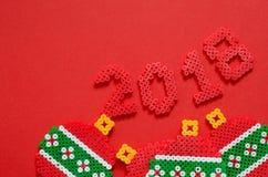 2018 zrobili od mini paciorkowatego ornamentu odizolowywającego na czerwonym tle z przestrzenią dla teksta Zdjęcie Stock