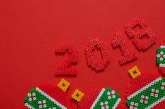 2018 zrobili od mini paciorkowatego ornamentu odizolowywającego na czerwonym tle z przestrzenią dla teksta Fotografia Royalty Free