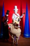 Zrozumiali istot pokrak muzycy Trzy chłopiec z Halloweenowym lub dziewczyny stawiają czoło maskę na czerwonym tle Obraz Stock