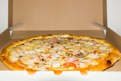 Zu bestellen Pizza Pizza geliefert in einen Koronakasten Frische Pizza gerade aus dem Ofen heraus lizenzfreies stockbild