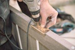 Zu das Scharnier befestigen Der Mann befestigt das Scharnier Verdrehen Sie die Abhängung von der Tür Installation von Türscharnie lizenzfreies stockbild