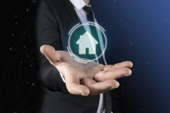 Zu einem Mann in einem Anzug und in einer Bindung in seinen Händen erscheint eine futuristische Grafik des Hauses Konzept von: Ha Lizenzfreie Stockbilder