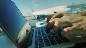 Zu einen Laptop am Flughafen benutzen Ein Mann, der auf einem Laptop etkst Hintergrundflugplatz mit Flächen schreibt stock video