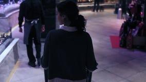 Zu entscheiden Rückseitengesamtlänge eines weiblichen Kostüms mit dem gelockten Haar, das hinunter den Gang in einem Supermarkt v stock video footage