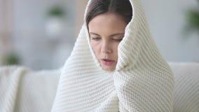 Zu Hause bedeckt mit dem einfrierenden Gefühl der jungen Frau des Plaids kalt stock video