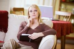 Zu Hause: Frau, die versucht, sich an Zeitplan-Daten zu erinnern Stockfoto