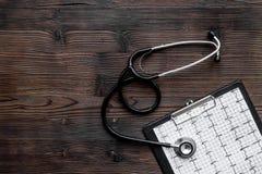 Zu Herzkrankheit bestimmen Kardiogramm, Stethoskop auf dunklem hölzernem copyspace Draufsicht des Hintergrundes stockbilder