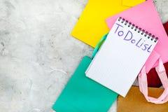 Zu Liste für den Einkauf am Notizbuch nahe Papiereinkaufstaschen auf grauem Draufsicht-Modell copyspace des Hintergrundes tun stockfoto