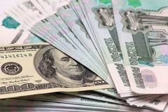 Zu tausend Rubelbanknoten und zu hundert Dollar Stockfoto