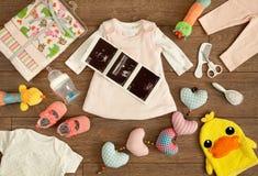 Zubehör des neugeborenen Babys und ihres Sonography-Druckes in der Ebenen-Lage-Zusammensetzung geschossen von oben Lizenzfreie Stockfotos