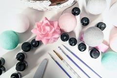 Zubehör für Nageldekoration, -bürsten und -lacke auf einer weißen Tabelle stockfotografie