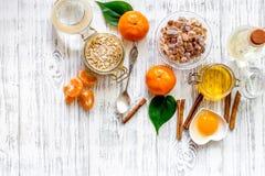 Zubereitung der gesunden Frühstückskost aus Getreide mit Orangen, Honig, Zimt auf copyspace Draufsicht des Holztischhintergrundes lizenzfreie stockfotos