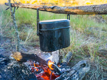 Zubereitung der Nahrung auf Lagerfeuer im wilden Kampieren Stockbilder