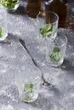 Zubereitung der tadellosen Medizin Bertical schoss Gläser und Minze in ihr, Flaschen Bourbon, Löffel auf dem grauen Bartisch lizenzfreies stockbild