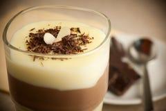 Zubereitung des Vanillepuddingnachtischs mit Schokoladensirup und Banan stockfoto