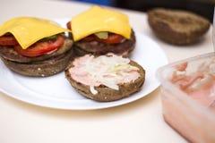 Zubereitung von köstlichen Burgern Chef, der Fleischburger mit Speck, Käse und Gemüse, selektiver Fokus kocht Nahaufnahme lizenzfreie stockfotografie