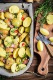 Zubereitung von Ofenkartoffeln mit Kräutern und Knoblauch Stockfotografie