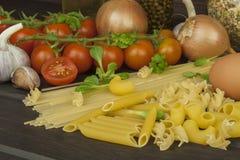Zubereitung von selbst gemachten Teigwaren Teigwaren und Gemüse auf einem Holztisch dietätische Lebensmittel Lizenzfreie Stockbilder