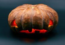 Zucca arancio di Halloween su fondo nero Decorazione del partito di Halloween Zucca scolpita con il fronte spaventoso ed il bagli fotografia stock