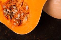 Zucca arancio fresca mezza su di legno nero Fotografie Stock