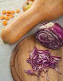 Zucca con le fette della carota, le mele ed il cavolo porpora su una tavola di legno Immagini Stock