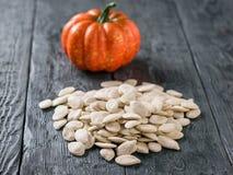 Zucca decorativa rotonda e un mazzo di semi di zucca su una tavola rustica Fotografie Stock Libere da Diritti