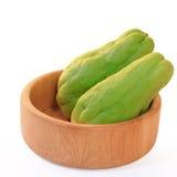 Zucca della zucchina centenaria, anche conosciuta come il choko in ciotola di legno su bianco Immagini Stock