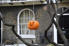 Zucca di Halloween appesa giù da un albero davanti ad una casa georgiana immagine stock