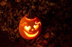 Zucca di Halloween che sorride con i cuori in foglie di autunno Immagini Stock Libere da Diritti