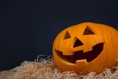 Zucca di Halloween con il fronte divertente sopra grey Immagini Stock Libere da Diritti