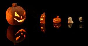 Zucca di Halloween con le candele brucianti su fondo nero immagini stock