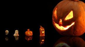 Zucca di Halloween con le candele brucianti su fondo nero immagini stock libere da diritti