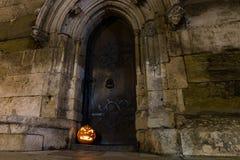 Zucca di Halloween davanti alla porta di legno antica ed alla parete di pietra di una chiesa, Germania Fotografia Stock Libera da Diritti