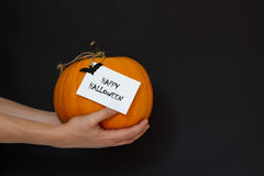 Zucca di Halloween a disposizione su un fondo nero Fotografia Stock