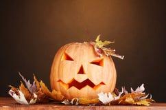Zucca di Halloween e fogli di autunno Fotografia Stock