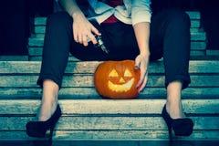 Zucca di Halloween e una ragazza che la spara con una pistola nella seduta sulle scala urbane Fotografia Stock