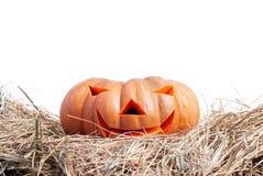 Zucca di Halloween sul fieno su un fondo bianco isolato Immagini Stock