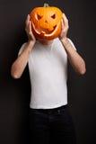Zucca di Halloween sulla testa dell'uomo Fotografia Stock