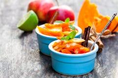 Zucca e mela caramellate in piccolo vaso sulla tavola di legno Fotografia Stock Libera da Diritti