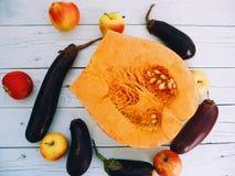 zucca mezza, melanzana e mele su un fondo bianco Fotografia Stock