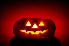 Zucca scarry arancione con gli occhi burning su colore rosso Fotografia Stock Libera da Diritti