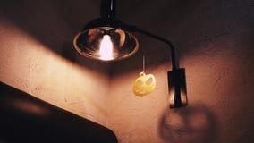 Zucca scolpita della carta di Halloween che appende sul colpo di medium della lampada video d archivio