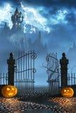 Zucche di Halloween accanto ad un portone di un castello spettrale Immagine Stock