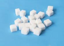 Zuccheri i cubi su fondo, su alimento e sul concetto blu di sanità, Se Immagine Stock