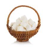 Zuccheri i cubi in un primo piano marrone del canestro di vimini isolato su bianco Immagine Stock