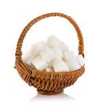 Zuccheri i cubi in un primo piano marrone del canestro di vimini isolato su bianco Immagine Stock Libera da Diritti