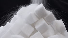 Zuccheri immergersi in su un mucchio dei cubi dello zucchero stock footage