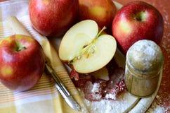 Zuccheri l'agitatore, le mele ed il coltello della buccia sul tagliere di legno Fotografia Stock
