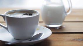 Zuccheri la caduta nella tazza di caffè sulla tavola di legno video d archivio