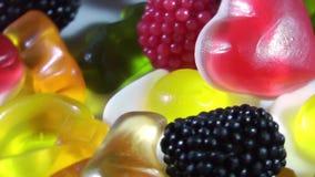 Zuccheri la caramella gommosa della gelatina di colore che gira sulla tavola archivi video